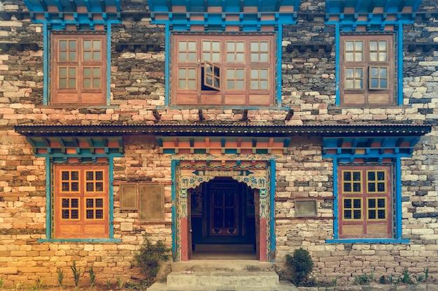 Fenêtres et porte de style népalais dans le vieux mur de briques