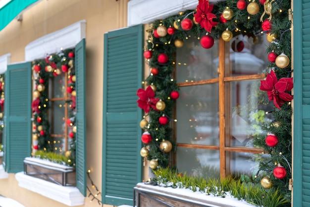Les fenêtres sont décorées de branches de sapin et de guirlandes de noël.