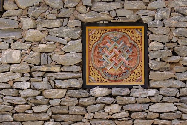 Fenêtres tibétaines de tradition et mur de pierre.