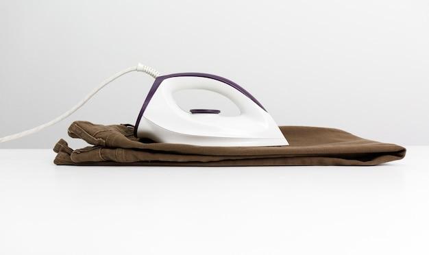 Fer blanc mis sur un jean marron et une table