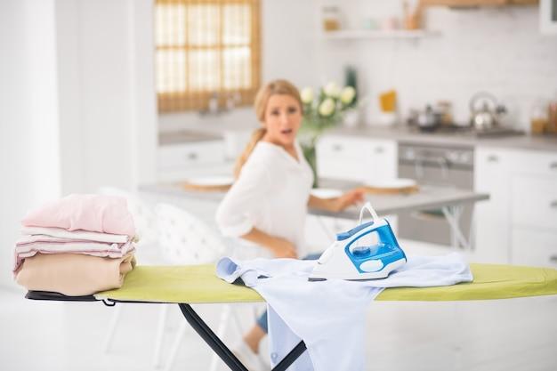 Fer chaud sur chemise blanche sur planche à repasser et femme assise avec grimace