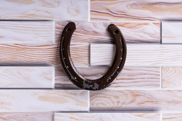 Fer à cheval en acier sur un bois, porte chance, symbole
