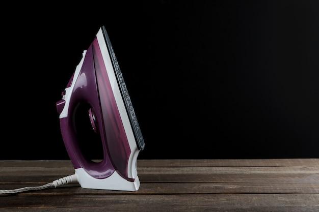 Fer lilas sur fond noir. repasser des vétements. appareils électroménagers. avec un espace pour le texte.
