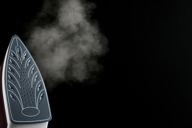 Le fer lilas libère de la vapeur sur fond noir. repasser des vétements. appareils électroménagers. avec un espace pour le texte