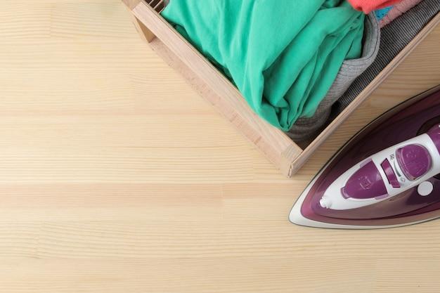 Fer lilas et une pile de vêtements dans une boîte sur un fond en bois naturel. vue de dessus avec place pour le texte. repasser des vétements. appareils électroménagers.