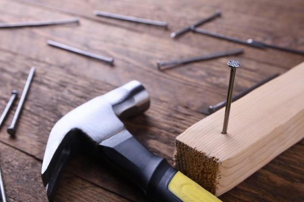 Fer à marteau, ruban centimétrique et clous sur table en bois