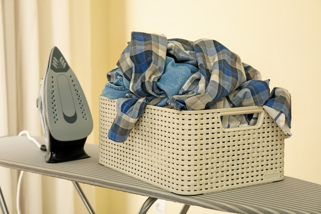 Fer et panier avec des vêtements sur planche à repasser