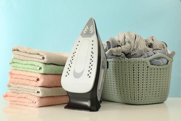 Fer à repasser moderne, blanchisserie et tas de serviettes sur table blanche