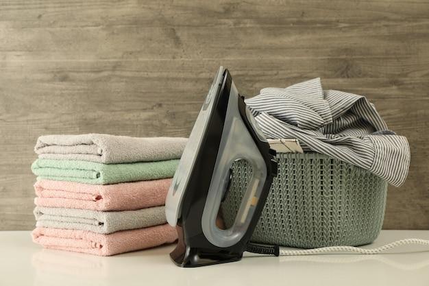 Fer à repasser, panier avec linge et tas de serviette contre bois