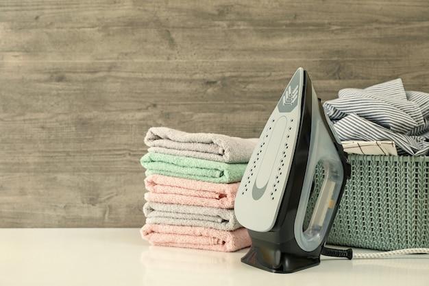 Fer à repasser, panier avec linge et tas de serviette sur fond de bois
