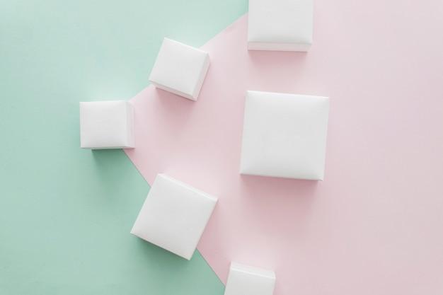 Fermé différentes boîtes blanches sur fond de papier rose et vert