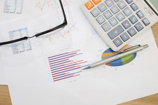 Fermé et flou sur stylo portant sur la paperasse avec calculatrice