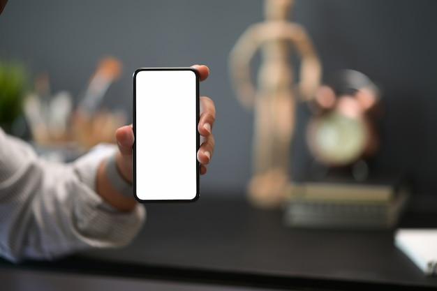 Ferme l'homme montrant un téléphone mobile à écran blanc dans l'espace de travail créatif