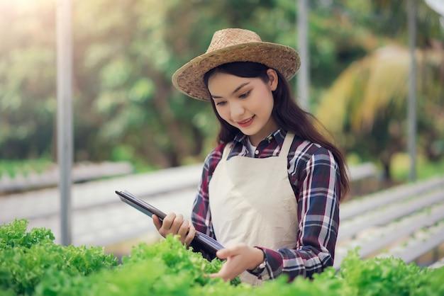 Ferme maraîchère hydroponique. beau fermier asiatique étudiant la culture et l'analyse de légumes hydroponiques. concept de culture de légumes biologiques et d'aliments naturels.