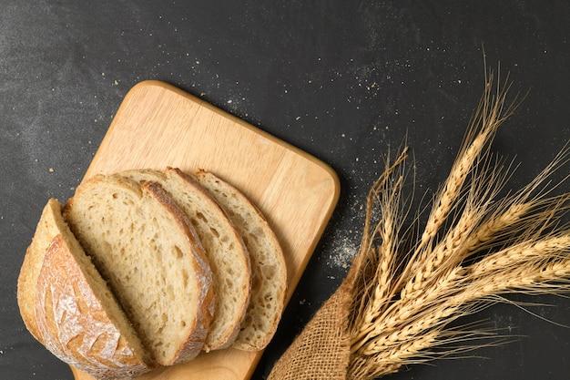Fermé de pain au levain sur plaque de bois et orge sèche sur table noire, concept de pain et de boulangerie