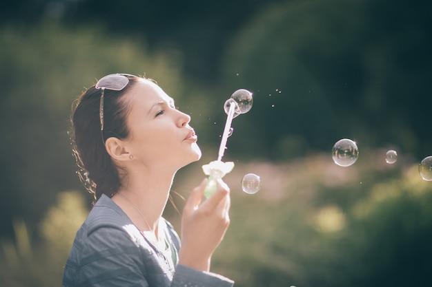 Fermer. belle jeune femme soufflant des bulles à l'extérieur.