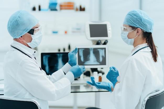 Fermer. collègues médicaux discutant d'une radiographie sur un écran de tablette numérique.