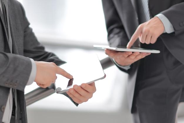 Fermer. deux hommes d'affaires avec des tablettes