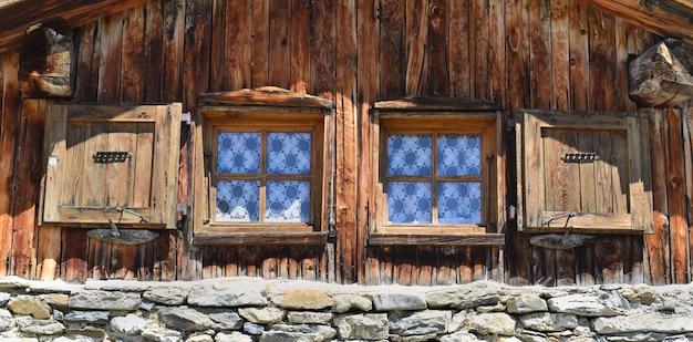Fermer sur deux petites fenêtres sur une façade de chalet de montagne
