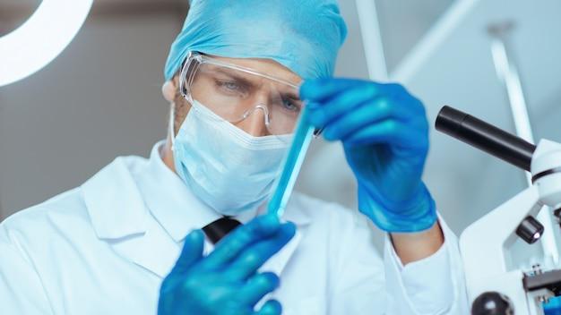 Fermer. échantillon du vaccin entre les mains du chercheur.
