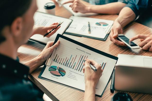 Fermer. employés discutant de documents financiers sur le lieu de travail. concept d'entreprise.