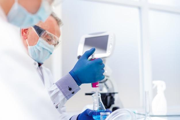 Fermer. les employés du laboratoire scientifique examinant le liquide dans un flacon de laboratoire.