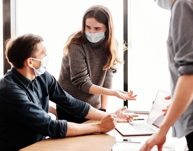 Fermer. employés portant des masques de protection discutant d'informations en ligne