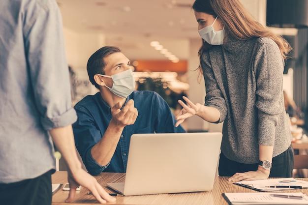 Fermer. employés portant des masques de protection discutant de problèmes de travail.