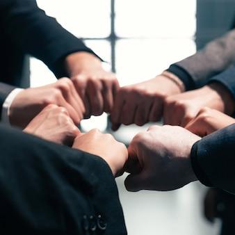 Fermer . équipe commerciale ambitieuse debout dans un cercle. le concept de travail d'équipe