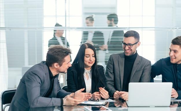 Fermer. l'équipe commerciale discute des données financières lors d'une réunion de bureau
