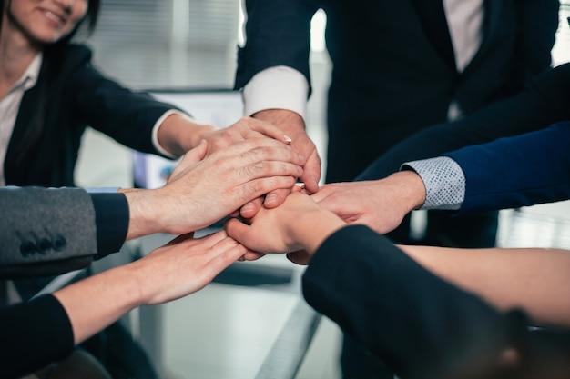 Fermer. équipe commerciale faisant une tour hors des mains. le concept de travail d'équipe