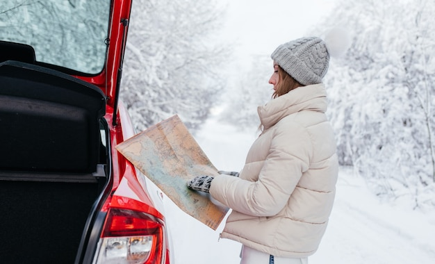 Fermer. femme tenant une carte dans ses mains lors de la recherche d'un itinéraire sur le bord de la route dans la forêt d'hiver