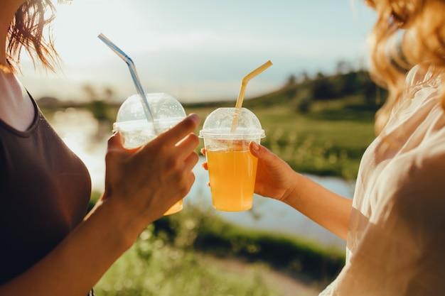 Fermer. femme tenant des tasses avec cocktail. avec de la paille, au coucher du soleil, expression faciale positive, en plein air