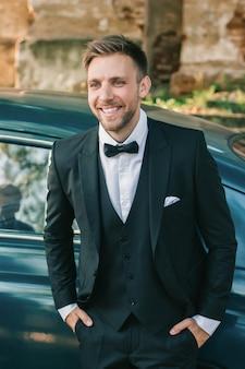 Fermer. le fier marié debout près de la voiture la voiture