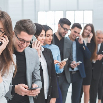 Fermer. un groupe de jeunes divers utilisent leurs smartphones