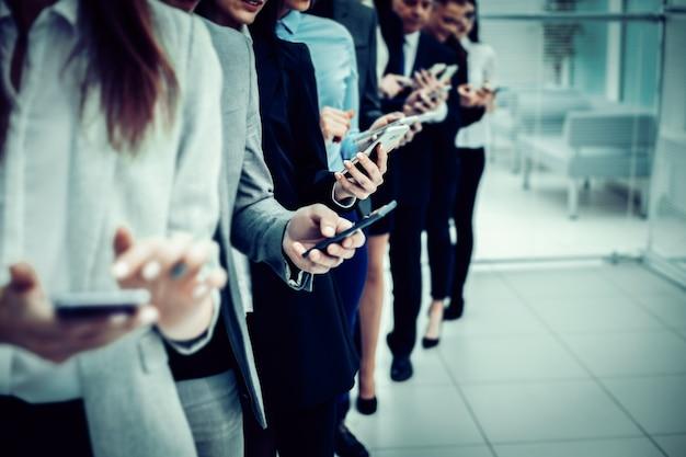 Fermer. un groupe de jeunes gens d'affaires regardant leurs écrans de smartphone