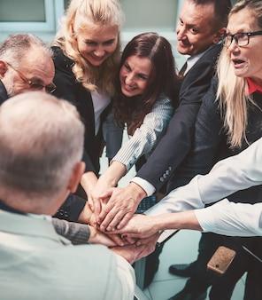 Fermer. heureux groupe d'employés faisant une pile de mains