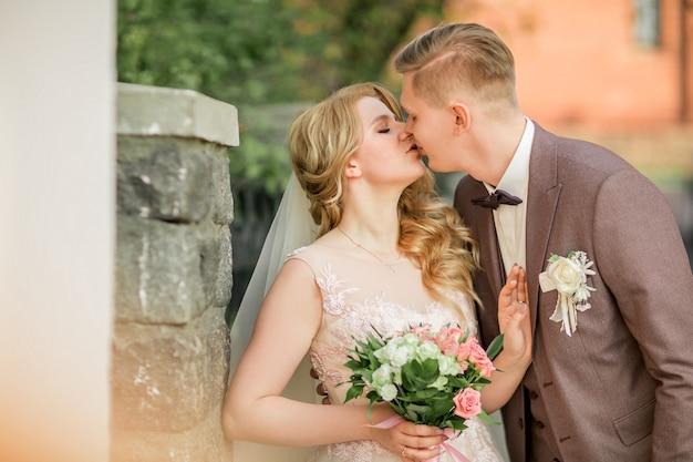 Fermer. heureux jeunes mariés s'embrassant debout dans la rue