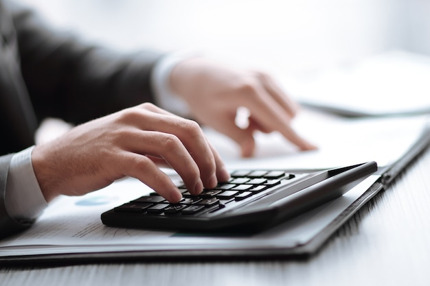 Fermer. l'homme d'affaires peut utiliser la calculatrice pour calculer le profit.