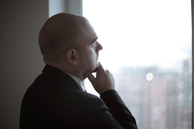 Fermer. homme d'affaires réfléchi regardant dans la fenêtre du bureau