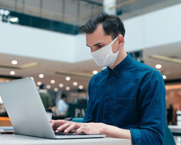 Fermer. homme d'affaires travaillant sur un ordinateur portable dans un bureau vide. concept de protection de la santé