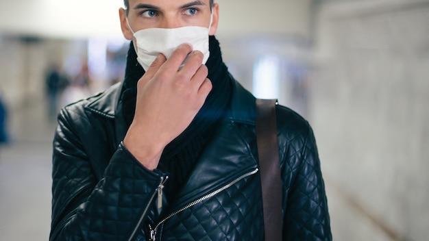 Fermer. un homme portant un masque de protection debout dans le passage à niveau du métro. coronavirus en ville