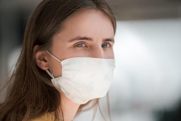 Fermer. une jeune femme dans un masque de protection vous regarde