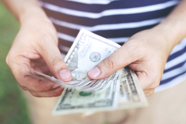 Fermer jeune homme debout tenir la main compter l'argent dispersé.