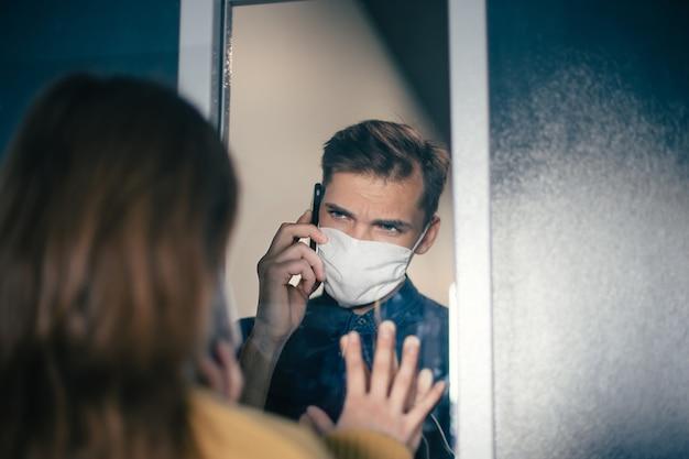 Fermer. un jeune homme et une femme se regardent anxieusement à travers la vitre. photo avec un espace de copie