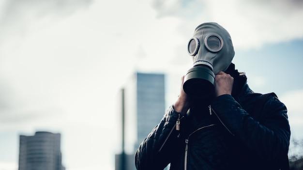 Fermer. jeune homme portant un masque à gaz dans une rue de la ville