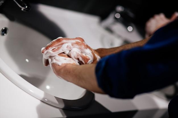 Fermer. jeune homme savonnant ses mains sous le robinet. hygiène et soins