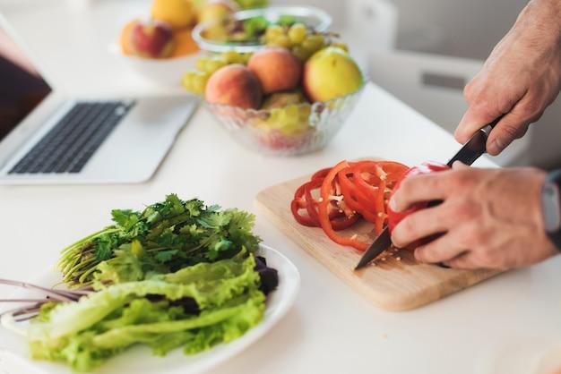 Fermer. jeune homme sportif prépare une délicieuse salade.