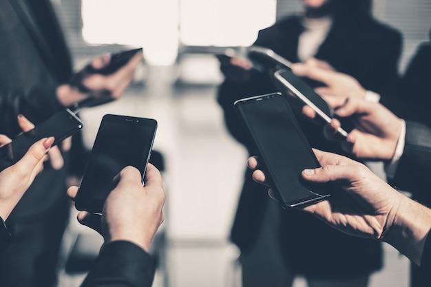 Fermer . les jeunes gens d'affaires regardant leurs écrans de smartphone. les gens et la technologie