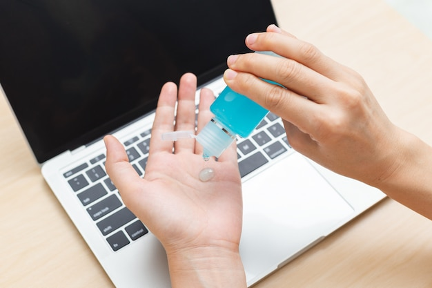 Fermer la main à l'aide d'un gel désinfectant pour la prévention de l'hygiène des mains contre le coronavirus avant de travailler avec un ordinateur portable à la maison